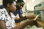 Two women operating a computer at a vocational training center in Harare, Zimbabwe